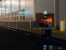Young engineer working during hignt shift otdoors in helmet Stock Images