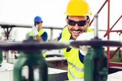 Oil worker closes the valve on the oil pipeline royalty free stock image