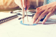 Young engineering man drawing compass on blueprints. Royalty Free Stock Photo