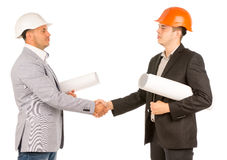 Young Engineers Shaking Hands Holding Blueprints Royalty Free Stock Photos