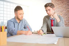 Young engineers at workplace. Two handsome businessmen doing paperwork in office. Young engineers at workplace Royalty Free Stock Images