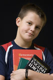 Young English student. Portrait of a teenage boy holding his English language books, black background Royalty Free Stock Photo
