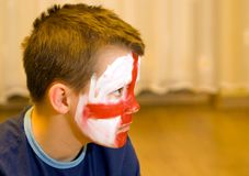 Young English team fan. A boy with the painted face, the English traditional flag colours. He is sitting on the floor. Watching TV. A concern on his face Royalty Free Stock Images