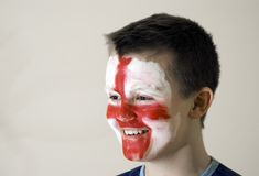 Young English team fan. A boy with the painted face, the English traditional flag colours. A smile on his face Stock Image
