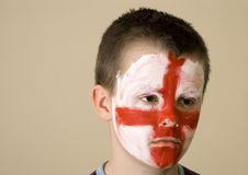 Young English team fan. A boy with the painted face, the English traditional flag colours. He's not very happy. A concern on his face Royalty Free Stock Photography