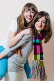 2 young enjoyable pretty women having fun friendly hugging and riding happy smiling & looking at camera. Portrait of two young beautiful ladies having fun royalty free stock images