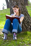 Young Enjoying A Book Royalty Free Stock Image