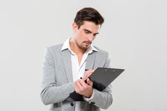 Young enterpreneur writing on clipboard Stock Images