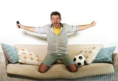 Young enthusiastic football fan celebrating goal crazy happy jumping on sofa couch at home watching soccer game on television hold. Ing remote in goal Royalty Free Stock Photos