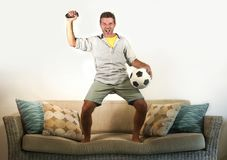 Young enthusiastic football fan celebrating goal crazy happy jumping on sofa couch at home watching soccer game on television hold. Ing ball and remote in goal Stock Photo
