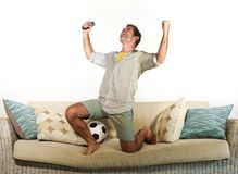 Young enthusiastic football fan celebrating goal crazy happy jumping on sofa couch at home watching soccer game on television hold. Ing ball and remote in goal Stock Images