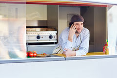 Young entrepeneur talking on the phone at his takeaway food stal. Male entrepeneur leaning on the counter and talking on the phone in his food stall where he Stock Photography