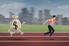 Young entrepreneur chased by bag of dollar Royalty Free Stock Photo