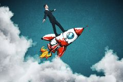Young entrepreneur concept. Businessman balancing on abstract drawn space ship on blue background with clouds. Young entrepreneur concept Stock Photos