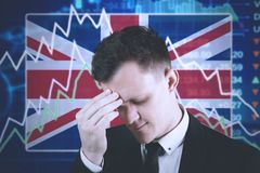 Young entrepreneur with declining finance graph. Young entrepreneur looks depressed with declining finance graph and England flag in the trade stock Stock Photography