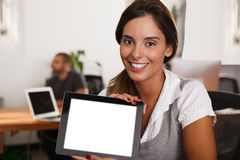 Young entrepreneur displaying her tablet computer. Young women entrepreneur displaying her tablet computer in her startup office Stock Photography