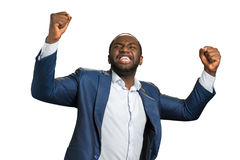 Young entrepreneur emotinally raised hands. Excited afro american businessman express satasfaction and triumph. Celebrating of victory Stock Images