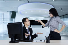 Young entrepreneur feels angry to her subordinate. Portrait of young entrepreneur feels angry to her subordinate while standing in the office Royalty Free Stock Photography