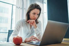 Young entrepreneur female using mobile laptop for looking a new business solution during work process at office.Blurred royalty free stock photos