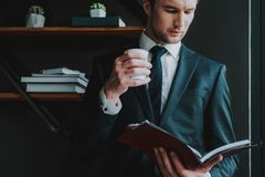 Young entrepreneur frowning and looking at notes while standing alone stock photo