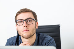 Young entrepreneur in his office. Man in glasses looking at camera while reflecting about business challenges. Concept of serious decision making Stock Image