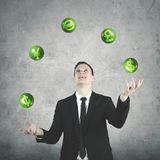 Young entrepreneur juggling with currency symbols. Image  of young male entrepreneur wearing formal suit while juggling with currency symbols Royalty Free Stock Photo