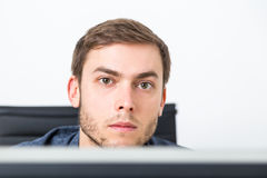 Young entrepreneur looking at screen. Handsome man looking at camera while sitting in armchair at his desk at office. Concept of decision making and analysis of Royalty Free Stock Photography