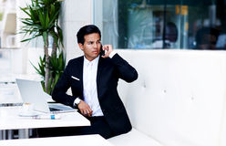 Young entrepreneur in a luxury black suit having cell conversation during work break in cafe Royalty Free Stock Image