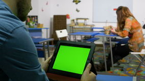 Young entrepreneur man using tablet pc with green screen in training room. Young entrepreneur man using tablet pc with green screen in a training room stock video footage