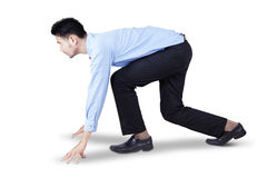 Young entrepreneur in ready position to run. Side view of young businessman in ready position to race and compete, isolated on white Stock Image