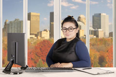 Young entrepreneur sits with computer on desk Stock Photos