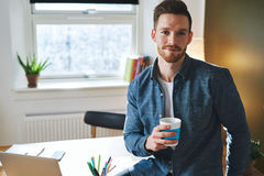Young entrepreneur sitting in his office Stock Photos