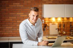 Entrepreneur sitting in his office holding cup of coffee smiling to camera. Young entrepreneur sitting in his office holding a cup of coffee smiling to the Royalty Free Stock Photography