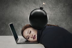 Young entrepreneur sleeps with bomb. Portrait of young entrepreneur sleeping on her laptop with a bomb over her head Royalty Free Stock Images