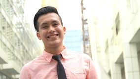 Young man smile cheerfully. Young entrepreneur smile cheerfully outdoor, urban background stock video