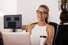 Young entrepreneur smiling in her startup office. Young woman entrepreneur sitting at her computer and smiling in her startup office Stock Photo