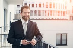 Young entrepreneur uses the phone on the balcony Stock Photos