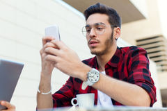 Young entrepreneur using his mobile phone at coffee shop. Outdoor portrait of young entrepreneur using his mobile phone at coffee shop Stock Photo