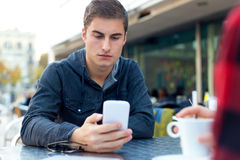 Young entrepreneur using his mobile phone at coffee shop. Royalty Free Stock Image