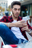 Young entrepreneur using his mobile phone at coffee shop. Royalty Free Stock Photography