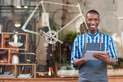 Young entrepreneur using a tablet in front of his cafe royalty free stock photography