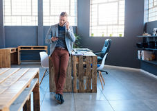 Young entrepreneur using a tablet and talking on his cellphone. Focused young businessman standing y himself in a large modern office talking on a cellphone and stock photos