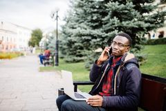 Young entrepreneur working on laptop and talk phone, sitting on wooden bench on the street. Freelancer. Young entrepreneur working on laptop and talk phone Stock Photos