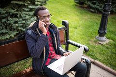 Young entrepreneur working on laptop and talk phone, sitting on wooden bench on the street. Freelancer. Young entrepreneur working on laptop and talk phone Stock Photo