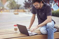Young entrepreneur working at the park outside on wooden bench.  Concept of successful busyness people Royalty Free Stock Image