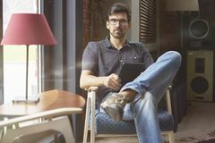 Young entrepreneur working on startup in modern office using digital tablet. Man wearing glasses and jeans, serious face. Young entrepreneur working on startup royalty free stock image