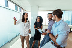 Young entrepreneurs discussing business ideas in boardroom. Business women presenting a business plan to her colleagues in boardroom. Men and women Stock Images