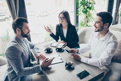 Young entrepreneurs are making a deal about their business, sitt. Ing in cafe with cups of coffee. Men is going to sign contract to complete the deal, discussing Royalty Free Stock Photography