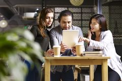 Young entrepreneurs meeting in company. Three young entrepreneurs meeting in company using digital tablet Royalty Free Stock Photos