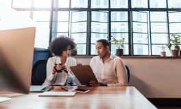 Young entrepreneurs sitting together at startup. Shot of two young entrepreneurs sitting together at office  desk. Man showing something on clipboard to women in Royalty Free Stock Photo